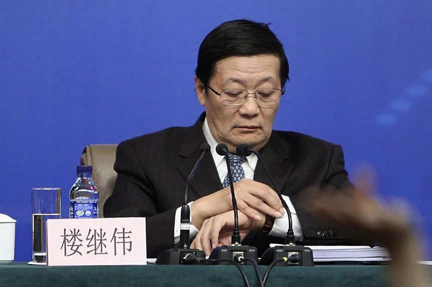 China's Finance Minister Lou Jiwei looks at his watch as a journalist (front) raises a hand to ask a question during a news conference, as a part of the National People's Congress (NPC) in Beijing, March 6, 2014. -- PHOTO: REUTERS