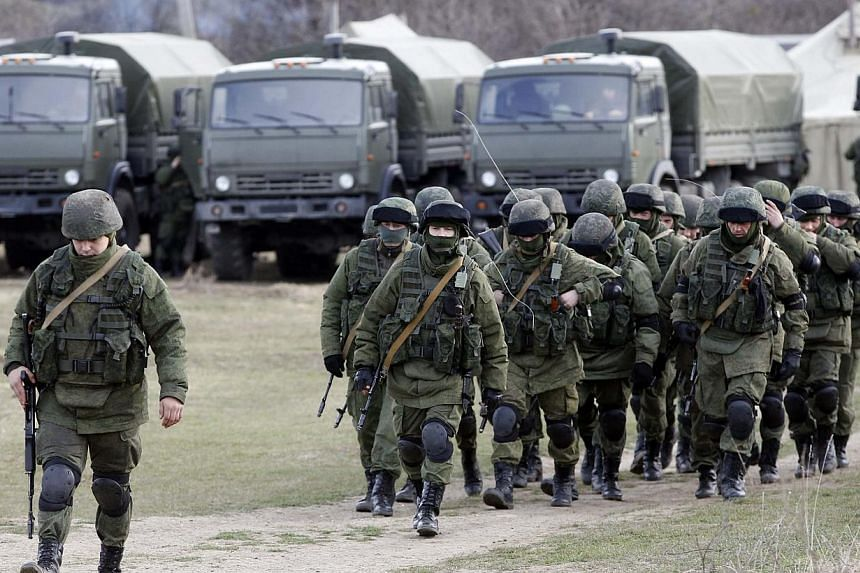 Uniformed men, believed to be Russian servicemen, walk in formation near a Ukrainian military base in the village of Perevalnoye outside Simferopol, on March 6, 2014. Gunmen were preventing a group of 40 military observers from the Organisation for S