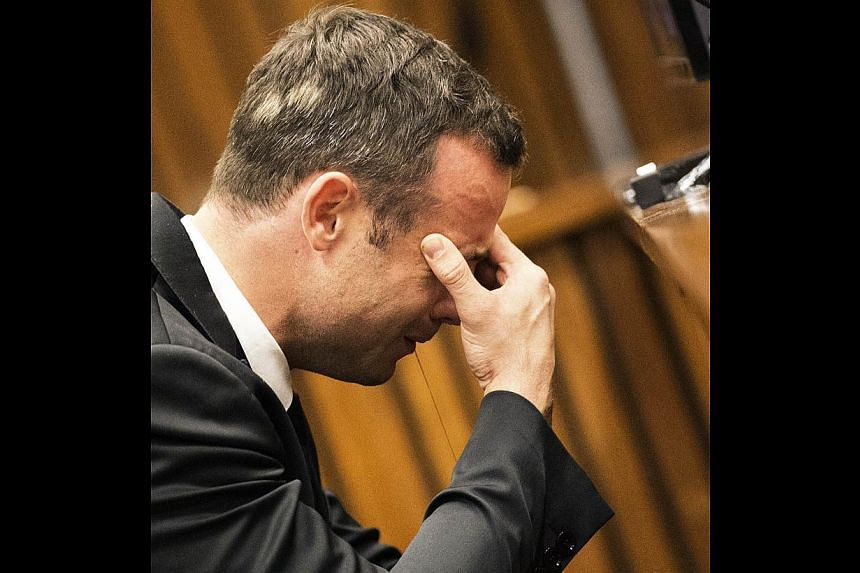 A weeping Oscar Pistorius shielded his ears as a witness in his murder trial on Thursday gave harrowing evidence about desperate attempts to save Reeva Steenkamp's life after she was shot. -- PHOTO: AFP
