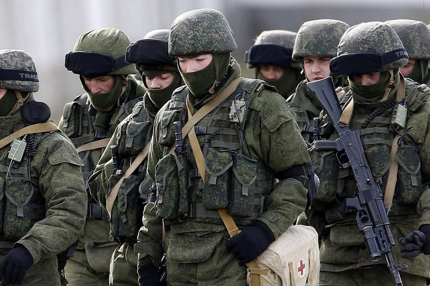 Uniformed men, believed to be Russian servicemen, walk in formation near a Ukrainian military base in the village of Perevalnoye outside Simferopol on March 6, 2014.The Ukrainian region of Crimea could adopt the Russian rouble as its currency a