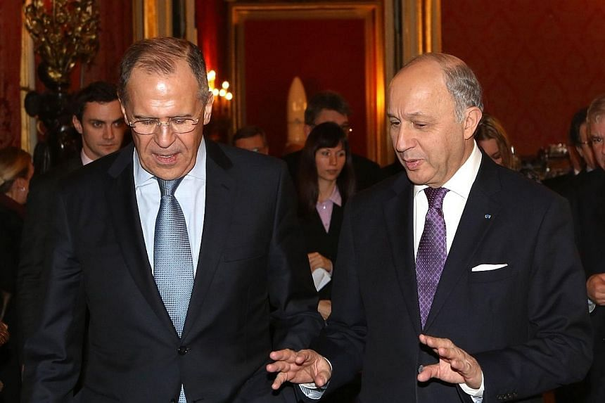 """A picture taken on March 5, 2014, shows Russian Foreign Ministeer Sergei Lavrov (left)talking to hisFrench counterpart, Mr Laurent Fabius,at the Elysee presidential palace in Paris.Mr Lavrov said attempts by """"our partners"""" to"""