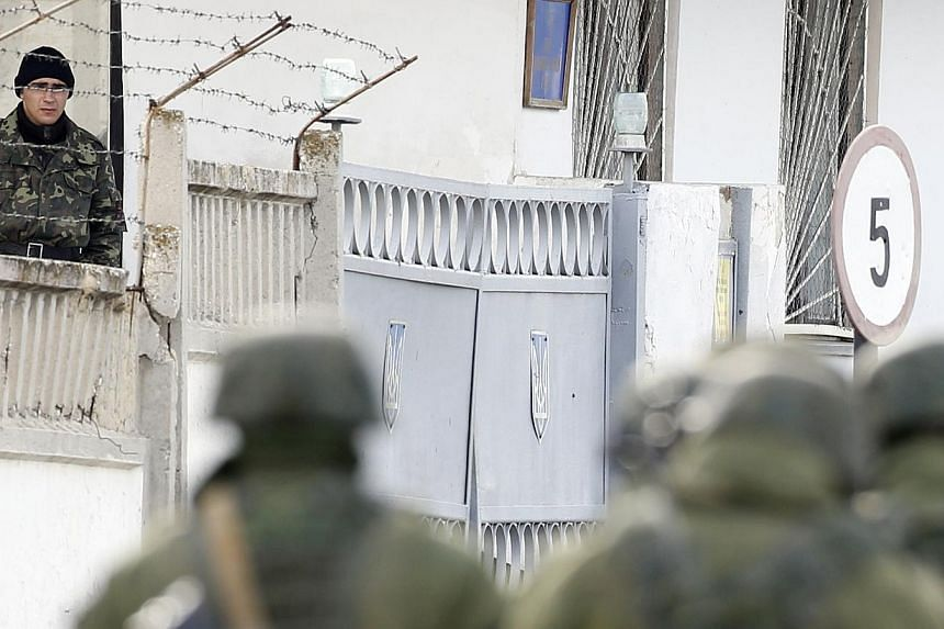 A Ukrainian serviceman watches uniformed men, believed to be Russian servicemen, passing by at a Ukrainian military base in the village of Perevalnoye outside Simferopol on March 6, 2014. Russia's Foreign Ministry said EU moves to consider freezing t