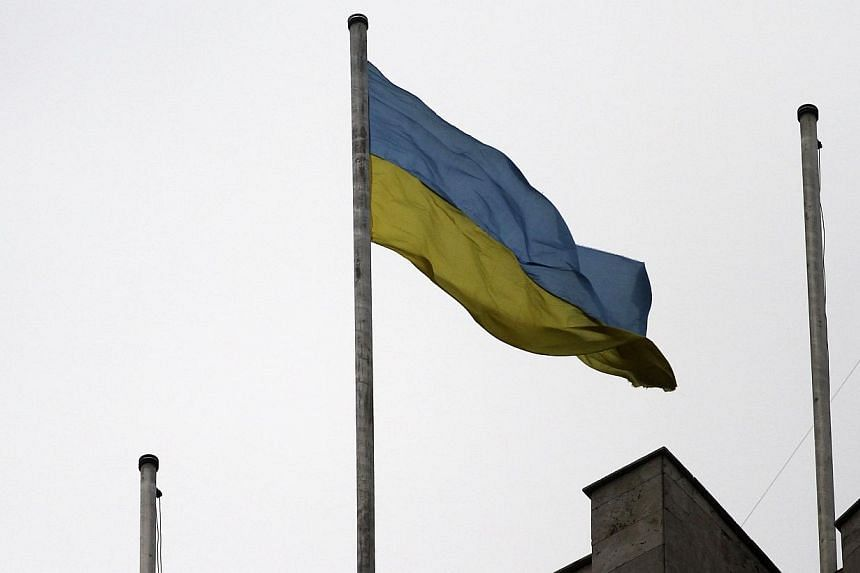 The Ukrainian flag flies on top of the regional administration building in the eastern Ukrainian city of Donetsk on Thursday, March 5, 2014. The police said pro-Moscow demonstrators who had seized the building had left overnight. -- PHOTO: REUTE
