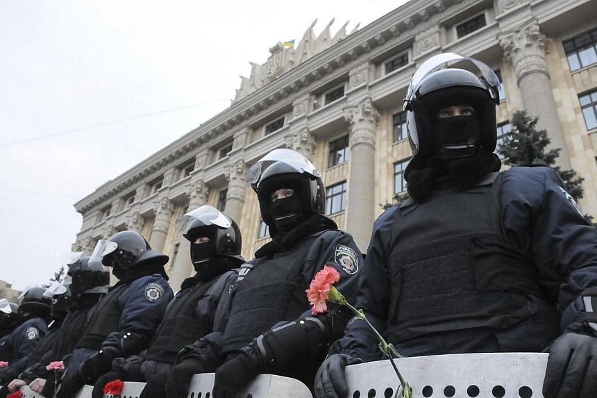 Riot police stand guard in front of regional government building as pro-Russian demonstrators take part in a rally in Kharkiv on March 5, 2014.Asian countries are not actively involved in the escalating crisis in Ukraine. But they are certainly