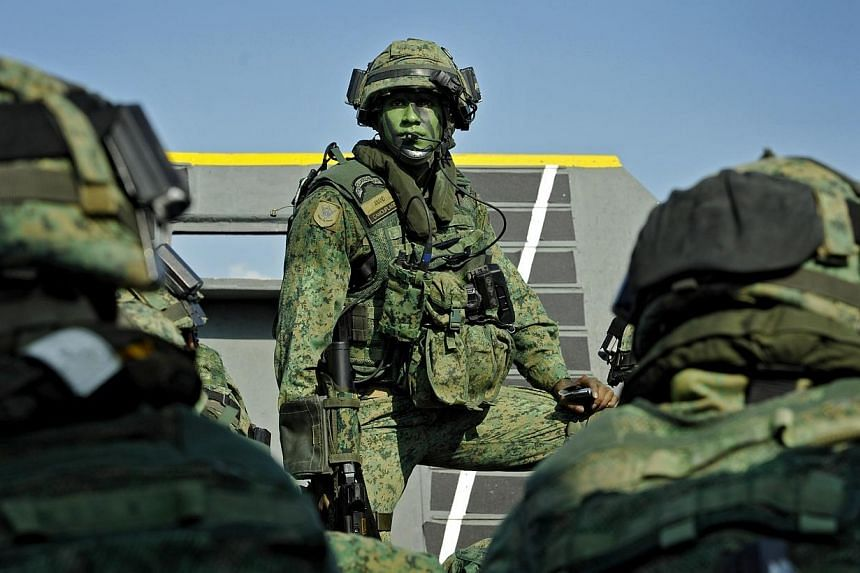 Servicemen from the Singapore Armed Forces (SAF) participating in a military exercise on Pulau Sudong on Aug 2, 2011.National Service stints may be shortened by a few weeks from the current two years, under a plan by the SAF to hire more career