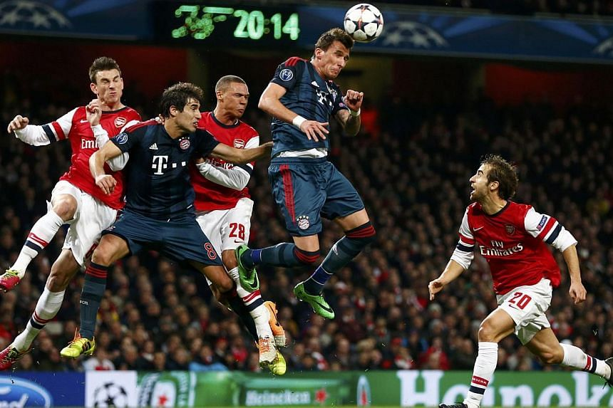 Bayern Munich's Mario Mandzukic (2nd right) and Javi Martinez (2nd left) jump for the ball next to Arsenal's Laurent Koscielny (left), Kieran Gibbs (centre) and Mathieu Flamini (right) during their Champions League round of 16 first leg soccer match