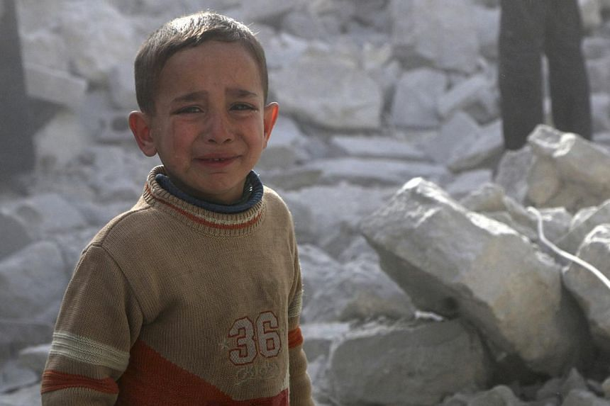 A boy cries as he stands amid rubble of collapsed buildings at a site hit by what activists said was a barrel bomb dropped by forces loyal to Syria's President Bashar al-Assad in Aleppo's al-Sakhour district on March 6, 2014.-- PHOTO: REUTERS