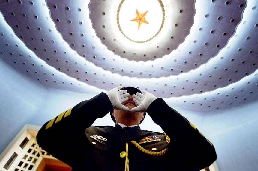 A Chinese People's Liberation Army (PLA) officer practices to conduct the military band before the opening session of the 12th National People's Congress (NPC) at the Great Hall of the People in Beijing on March 5, 2014. -- PHOTO: AFP