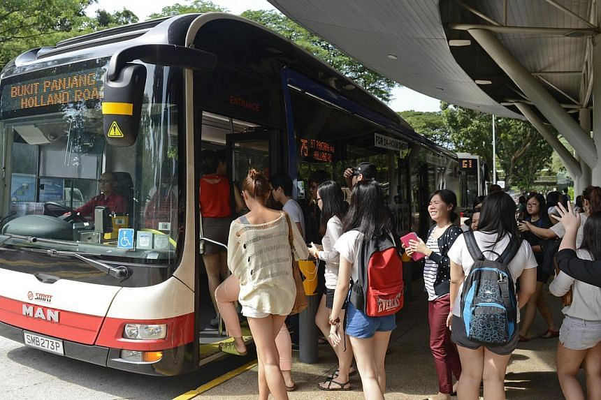 Students at a bus stop outside Ngee Ann Polytechnic in 2013. The Government plans to increase the bursaries and raise income eligibility threshold for students studying in institutes of higher learning this year, said Education Minister Heng Swee Kea