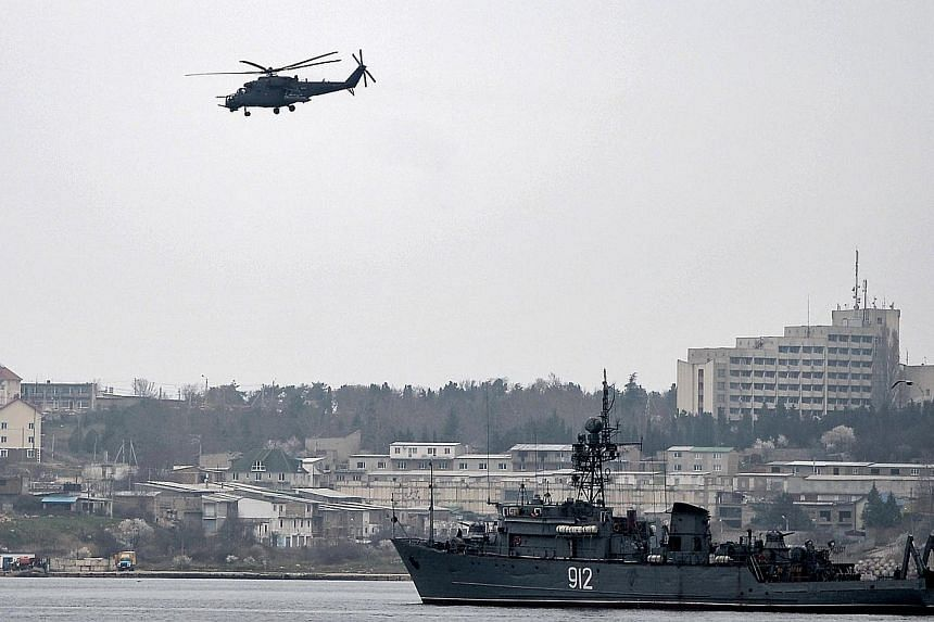 A Russian Mi24 military helicopter flies over the Russian navy minesweeper ship Turbinist in the harbour of Sevastopol, on March 7, 2014. Armed men at a checkpoint flying the Russian flag blocked Organisation for Security and Cooperation in Europe (O