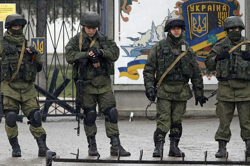 Uniformed men, believed to be Russian servicemen, stand guard outside a Ukrainian military base in the village of Perevalnoye outside Simferopol, on March 7, 2014. RussianPresident Vladimir Putin rebuffed a warning from US President Barack Obam