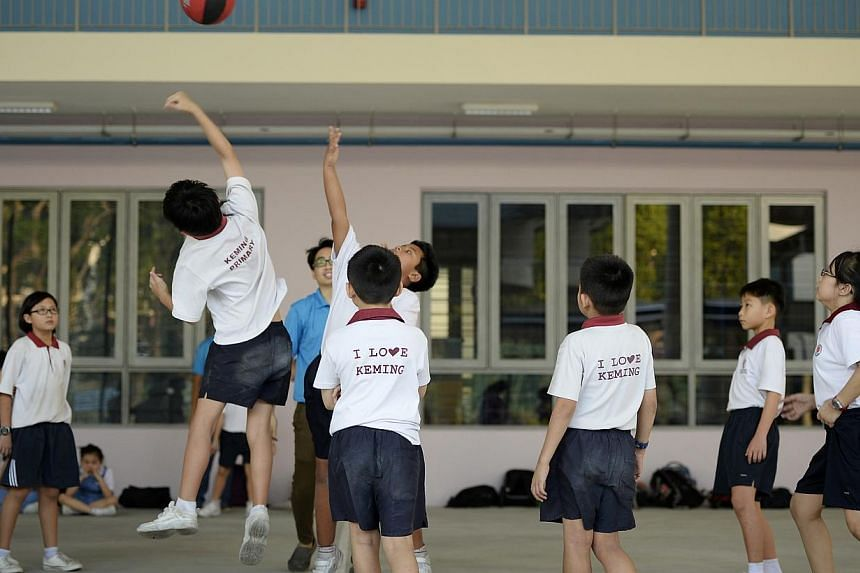 Pupils from Keming Primary School, who are part of a student care centre, having a game of basketball.Student care centres, which provide before- and after-school services such as homework supervision for pupils, are set to become a standard fe