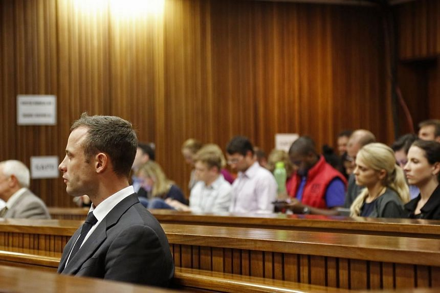 """South African paralympic athlete Oscar Pistorius (left) attends the fifth day of his trial for the 2013 murder of his girlfriend Reeva Steenkamp, at the high court in Pretoria, on March 7, 2014.Pistorius told security at his estate that """"everyt"""