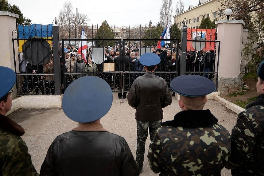 """Ukranian pro-Russian protesters demonstrate outside the air base in Belbek, near Sevastopol, on March 6, 2014.Russia's parliament will respect the """"historic choice"""" to be made by Crimea when the Ukrainian region's people vote in a referendum on"""