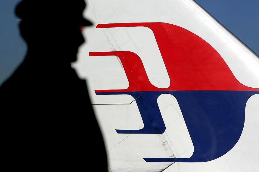 A file photo taken on July 5, 2005 shows a man silhouetted against a Malaysian Airlines plane tail as he looks out through a window at Sydney International Airport. -- FILE PHOTO: AFP