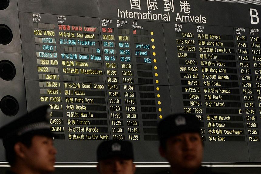 Chinese police stand beside the arrival board showing the flight MH370 (top-red) at the Beijing Airport after news of the Malaysia Airlines Boeing 777-200 plane disapeared on March 8, 2014. -- PHOTO: AFP