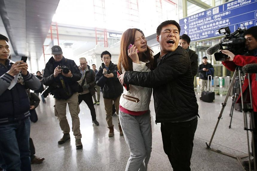 A relative (woman in white) of a passenger onboard Malaysia Airlines flight MH370 cries as she talks on her mobile phone at the Beijing Capital International Airport in Beijing on March 8, 2014. -- PHOTO: REUTERS
