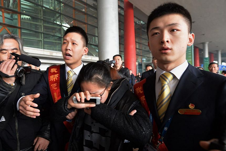 A crying woman is escorted to a bus for relatives at the Beijing Airport after news of the missing Malaysia Airlines Boeing 777-200 plane on March 8, 2014. -- PHOTO: AFP