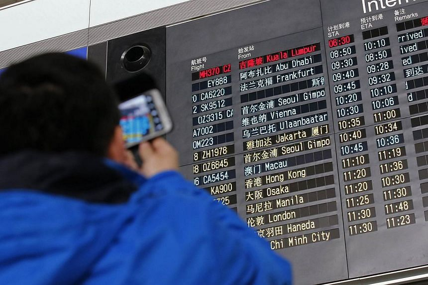 A man takes pictures of a flight information board displaying the Scheduled Time of Arrival (STA) of Malaysia Airlines flight MH370 (top, in red) at the Beijing Capital International Airport in Beijing, March 8, 2014. -- PHOTO: REUTERS