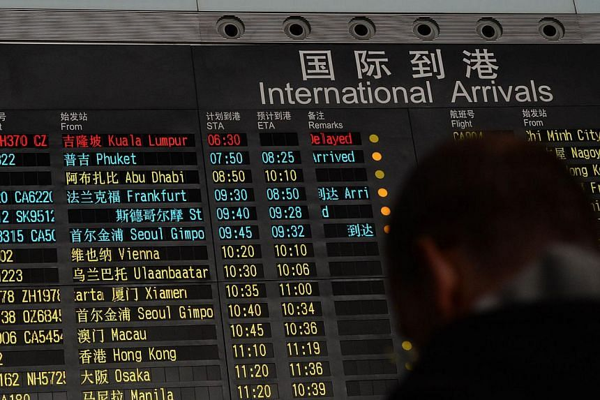A man stands beside the arrival board showing the flight MH370 (top-red) at the Beijing Airport after news of the Malaysia Airlines Boeing 777-200 plane disapeared on March 8, 2014. -- PHOTO: AFP