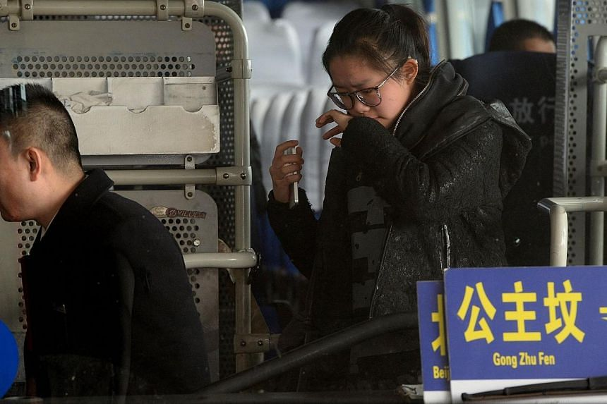 A crying woman is escorted to a bus for relatives of passengers of a missing Malaysia Airlines flight at Beijing International Airport in Beijing on March 8, 2014. -- PHOTO: AFP