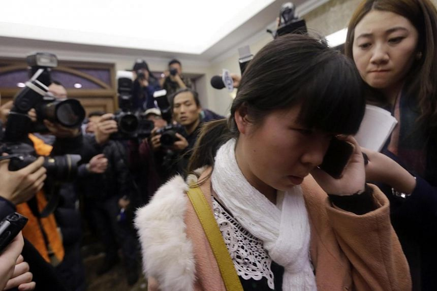 A relative of a passenger of Malaysia Airlines flight MH370 talks on a mobile phone as journalists attempt to interview her at a hotel in Beijing, March 8, 2014. -- PHOTO: REUTERS