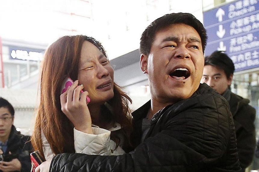 A relative of a passenger onboard Malaysia Airlines flight MH370 cries as she talks on her mobile phone at the Beijing Capital International Airport, March 8, 2014. -- PHOTO: REUTERS