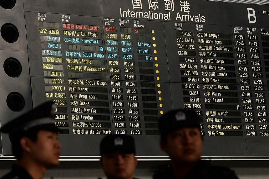 Chinese police stand beside the arrival board showing the flight MH370 at the Beijing Airport after news of the Malaysia Airlines Boeing 777-200 plane disapeared on March 8, 2014. -- PHOTO: AFP