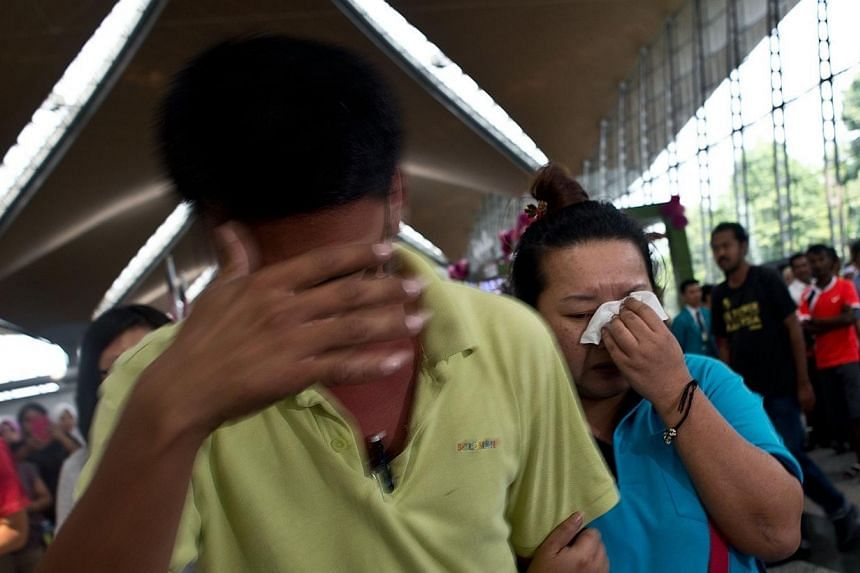 A woman breaks down while leaving the reception centre for families and friends after a Malaysia Airlines plane went missing at the Kuala Lumpur International Airport on March 8, 2014. -- PHOTO: AFP