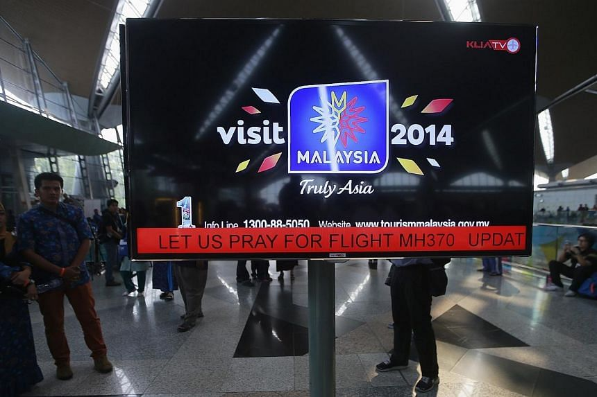 "An information screen displays a message ""Let Us Pray For Flight MH370"" at Kuala Lumpur International Airport in Sepang, March 8, 2014. . -- PHOTO: REUTERS"