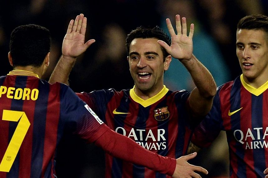 Barcelona's Xavi Hernandez (centre) celebrates with Pedro Rodriguez (left) and Cristian Tello after scoring against UD Almeria at the Camp Nou stadium in Barcelona on March 2, 2014. Xavi, who has won 22 trophies in 16 glittering seasons with Bar