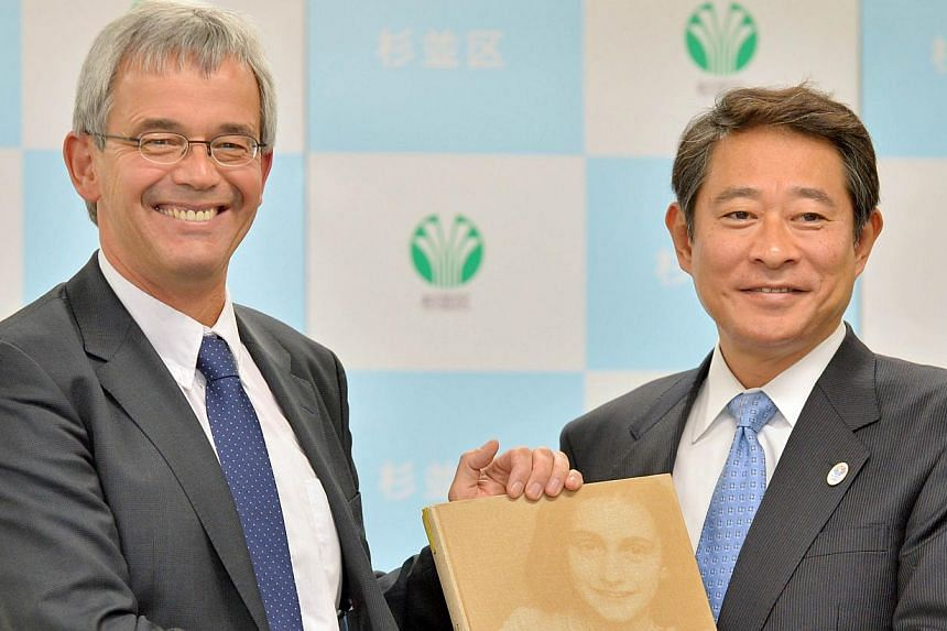 Anne Frank House international department head Jan Erik Dubbelman (left) shakes hands with Suginami mayor Ryo Tanaka during the presentation ceremony of a catalogue on the life of Anne Frank in Tokyo, on March 8, 2014. The Anne Fr