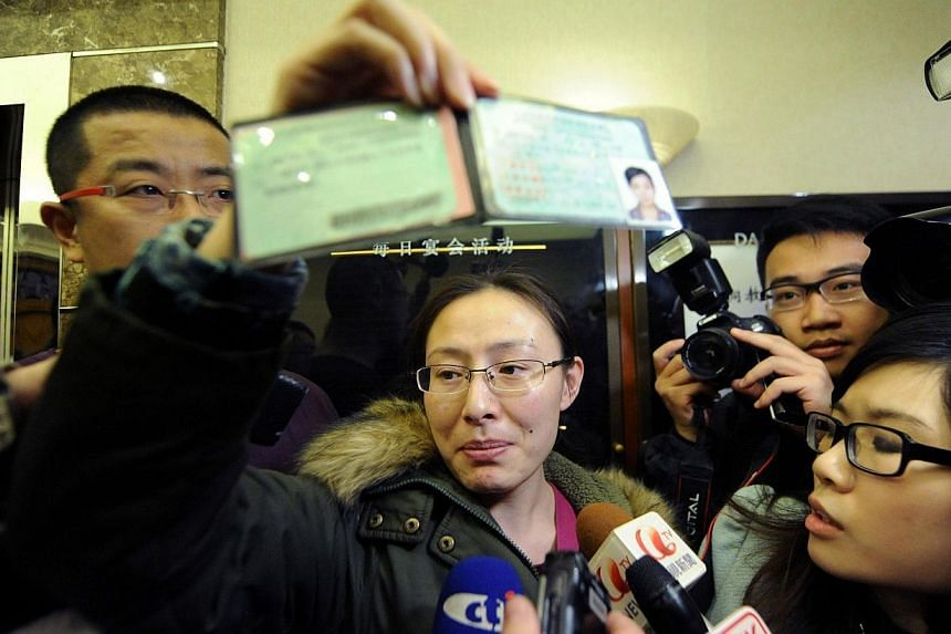 A woman displays the driver's licence of a friend who may be a passenger on board the missing Malaysia Airlines flight at a hotel in Beijing, on March 8, 2014. -- PHOTO: AFP
