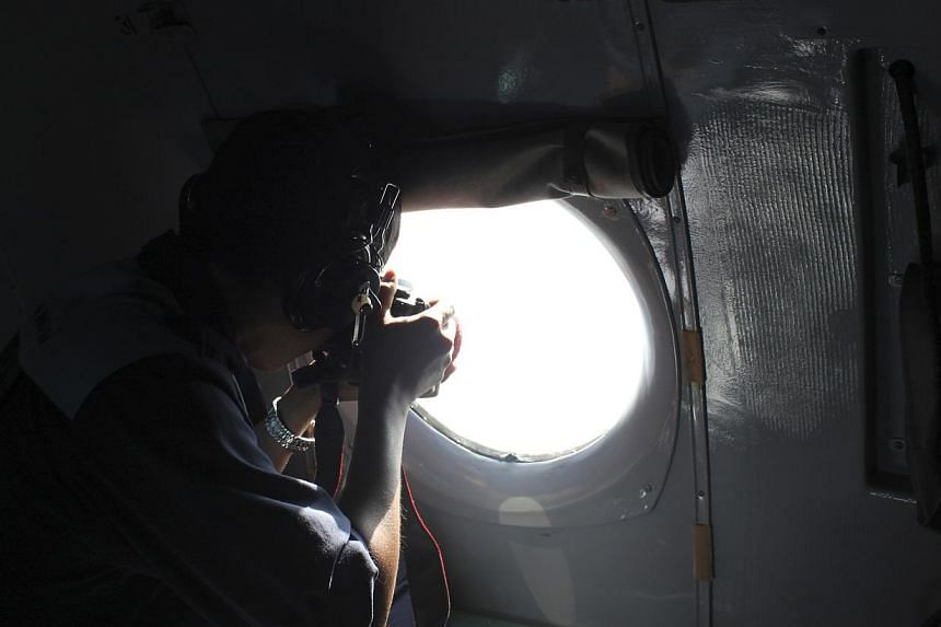 A Vietnamese Air Force officer takes photos from a search and rescue aircraft in the search area for a missing Malaysia Airlines plane, 250km from Vietnam and 190km from Malaysia, on March 8, 2014. Malaysian authorities have reviewed all CCTV recordi