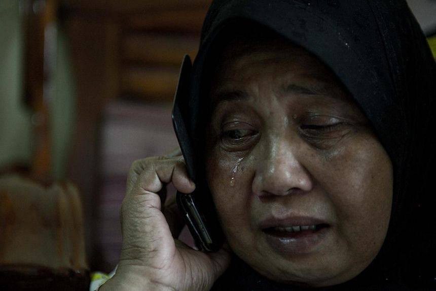 A relative of passengers on a missing Malaysia Airlines Boeing 777-200 plane cries at their house in Kuala Lumpur, on March 8, 2014. -- PHOTO: AFP