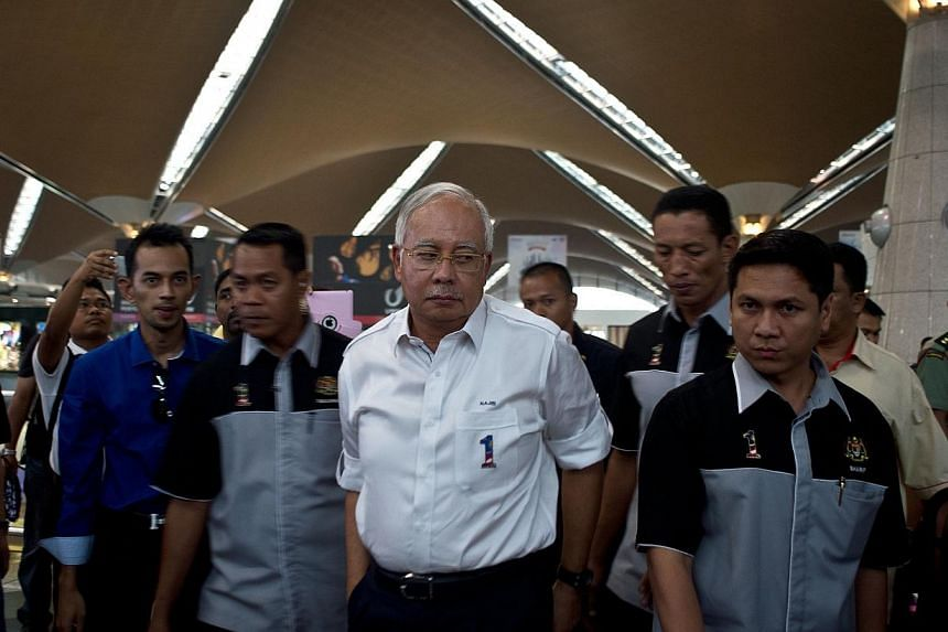 Malaysian Prime Minister Najib Razak (centre) arrives to meet family members of missing passengers at the reception centre at Kuala Lumpur International Airport, on March 8, 2014. -- PHOTO: AFP