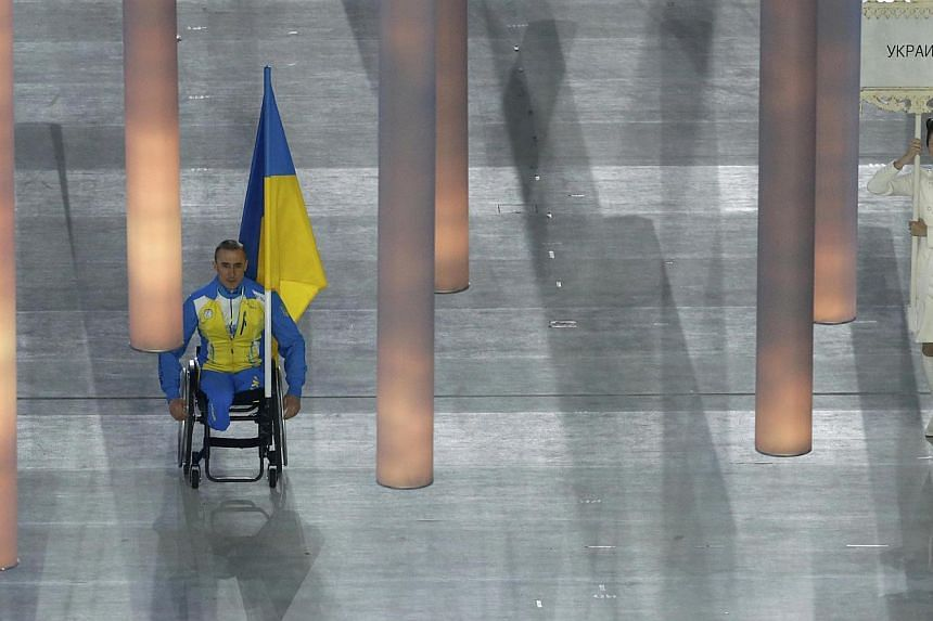 Ukraine's flag-bearer Mykhaylo Tkachenko arrives in the stadium during the opening ceremony of the 2014 Paralympic Winter Games in Sochi, on March 7, 2014.The 37-year-old skier and biathlete was the only Ukrainian competitor to take part in the