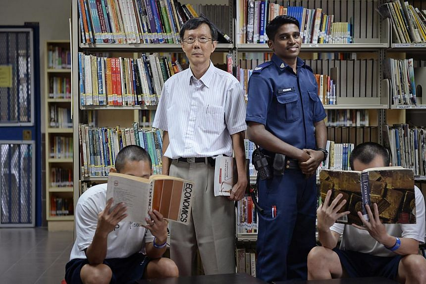 "Teacher Lee Chee Khuen (standing, in white) and Corporal Peranban Kumar with prison school students ""Alex"" (far left) and ""John"" (far right). Both scored distinctions in  last year's A-level exams."