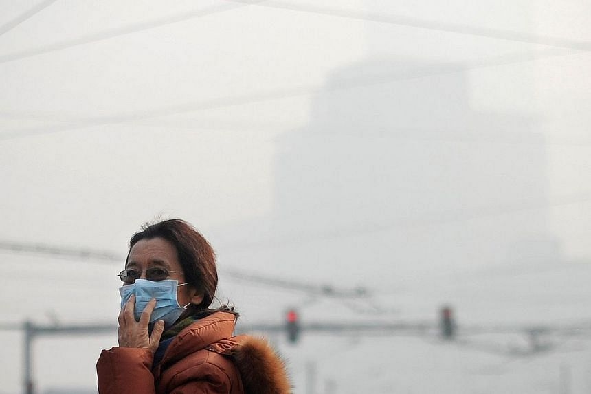 A woman wearing a face mask makes her way along a street in Beijing on Jan 16,2014. China tested on March 8, 2014, a domestically-produced drone aircraft designed to disperse smog, official media reported, in an important step for the country's