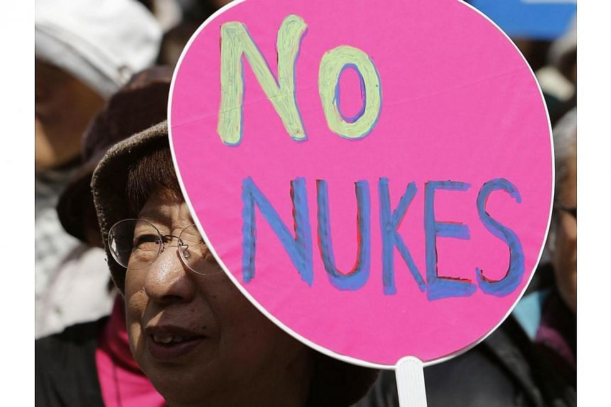 """An anti-nuclear protester holds a paper fan saying """"No Nukes"""" before a march by protesters in Tokyo on March 9, 2014. -- PHOTO: REUTERS"""