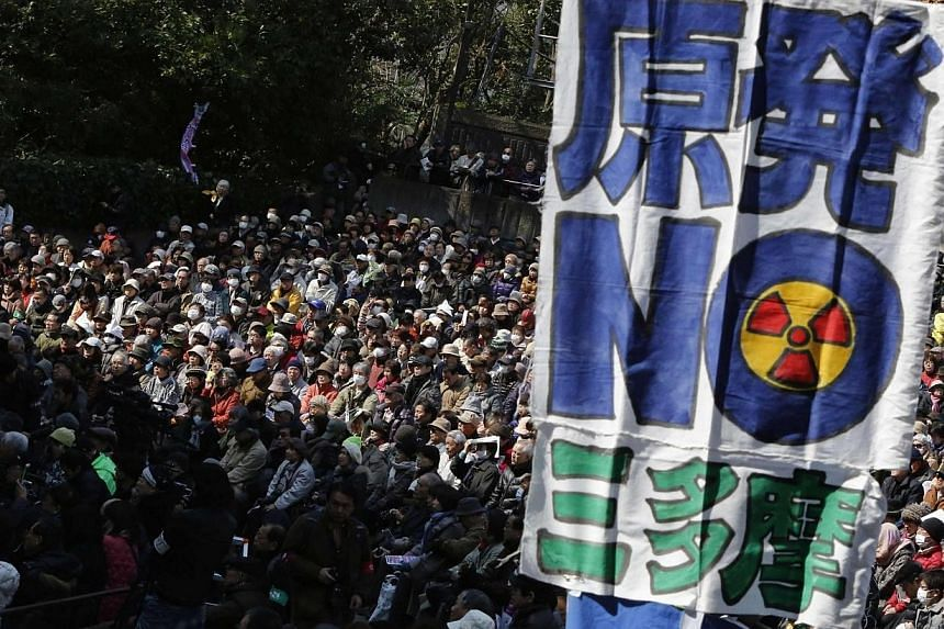 """Anti-nuclear protesters are seen behind a banner saying """"No Nukes"""" before they march in Tokyo on March 9, 2014. -- PHOTO: REUTERS"""