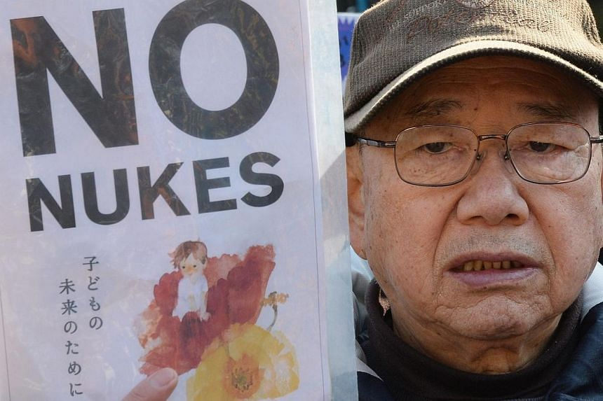 """A man holds a placard reading """"No Nukes"""" during a rally denouncing nuclear power plants in front of the National Diet in Tokyo on March 9, 2014. --PHOTO: AFP"""