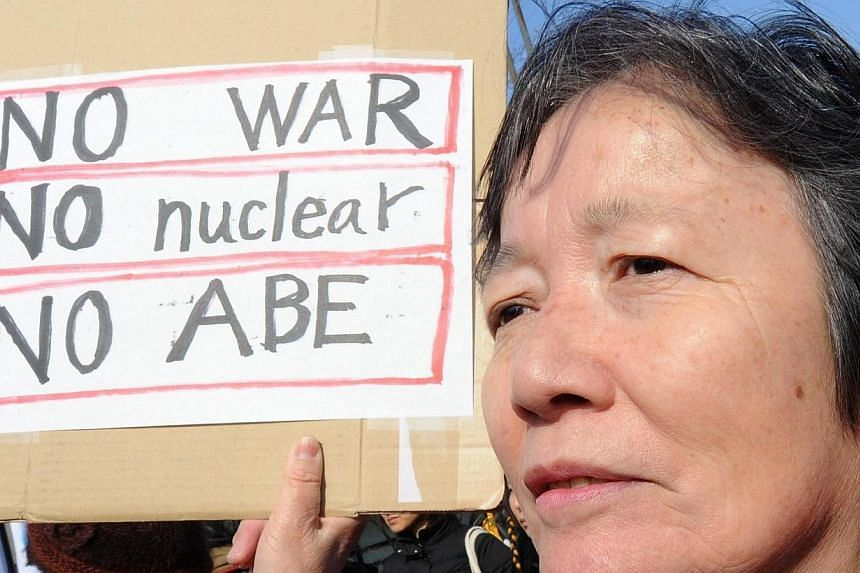 A woman holds a placard during a rally denouncing nuclear power plants in front of the National Diet in Tokyo on March 9, 2014. -- PHOTO: AFP