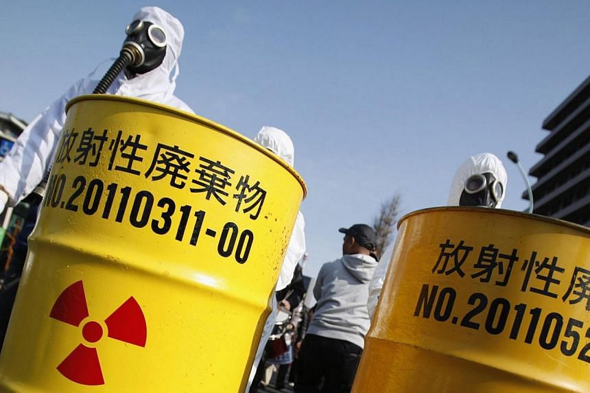 Anti-nuclear protesters wearing protective suits push mock drums which are labelled as radioactive waste from Kansai Electric Power Co's Ohi nuclear power plant (left) and Tokyo Electric Power Co's (TEPCO) Fukushima nuclear power plant, as they march