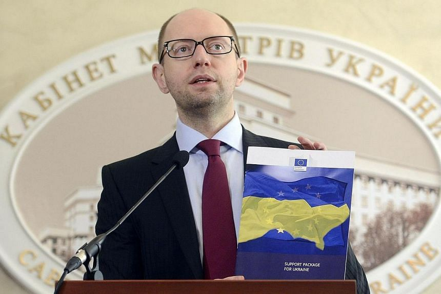 This handout picture released by Ukraine's Prime minister press office and taken on March 7, 2014 shows Ukraine's Prime Minister Arseniy Yatsenyuk displaying a folder with documents related to the European Union Support package for Ukraine during a p