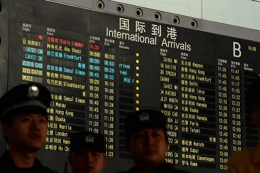Chinese police stand beside the arrival board showing the flight MH370 at the Beijing Airport after news of the Malaysia Airlines Boeing 777-200 plane disapeared on March 8, 2014. A Texas semiconductor firm said that 20 of its employees were confirme