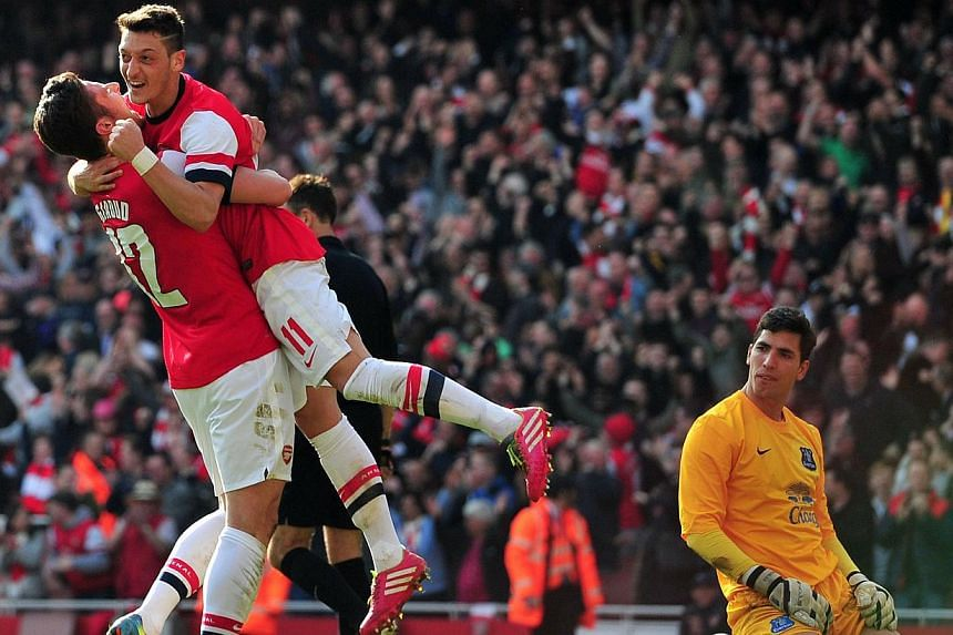 Arsenal's French striker Olivier Giroud (left) celebrates scoring the fourth goal with German midfielder Mesut Ozil (centre) during the English FA Cup quarter final football match between Arsenal and Everton at the Emirates Stadium in London on March