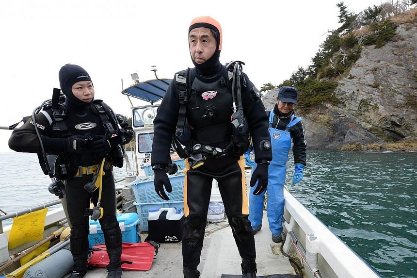 Yasuo Takamatsu (centre) and an instructor (left) head for a diving spot by boat in Onagawa, Miyagi Prefecture on March 2, 2014.-- FILE PHOTO: AFP