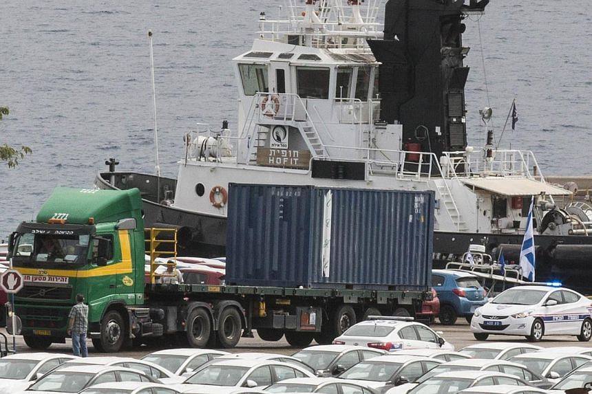 Military police escorts a truck carrying a container to a nearby navy base on Sunday, March 9, 2014 at the southern Israeli port of Eilat, where Israeli army started to unload the Panamanian-flagged Klos-C that was allegedly transporting arm from Ira