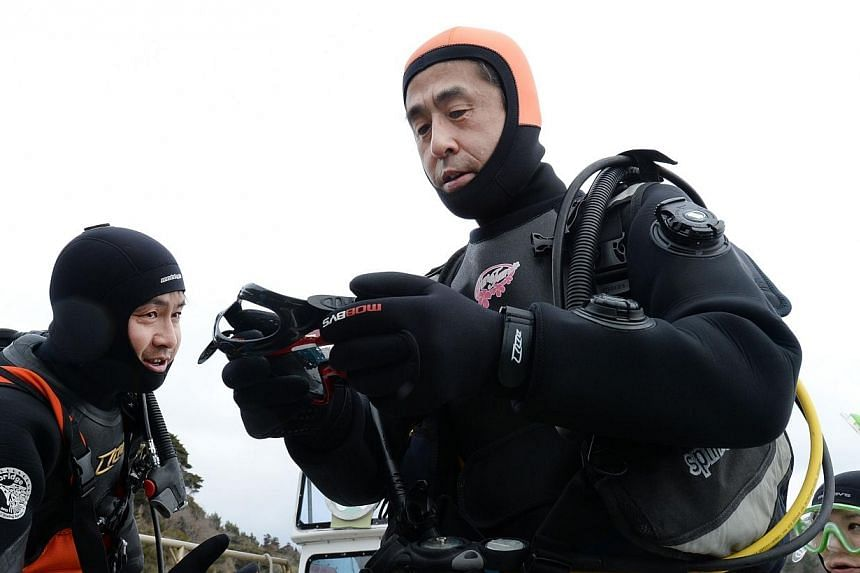 Instructors help Yasuo Takamatsu (centre) checks his gears as they head for a diving spot by boat in Onagawa, Miyagi Prefecture on March 2, 2014.-- FILE PHOTO: AFP